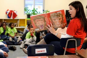 A photo of a teacher reading a book to children.