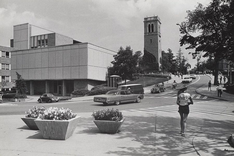Black and white photo of Social Sciences Building with cars driving down the street and students walking on the sidewalk from the 1960s.