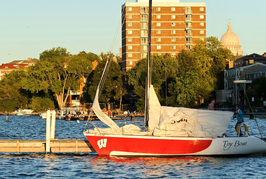A UW Hoofer sailboat on lake Mendota during the sunset.
