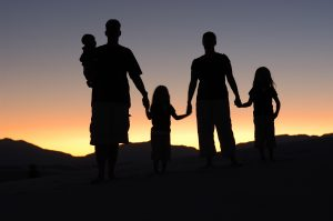 A silhouette of a family holding hands and looking at a sunset.